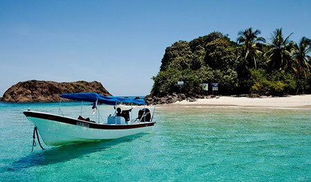 A small boat in the turquoise of Coiba, Panama