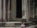 A child sits cross-legged outside a stone temple in Angkor Wat, Cambodia