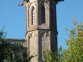 A church tower rises above the trees