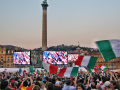 Italian football fans watch a game on outdoor screens.