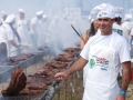 A chef in a white hat barbeques meat in traditional Uruguayan style.