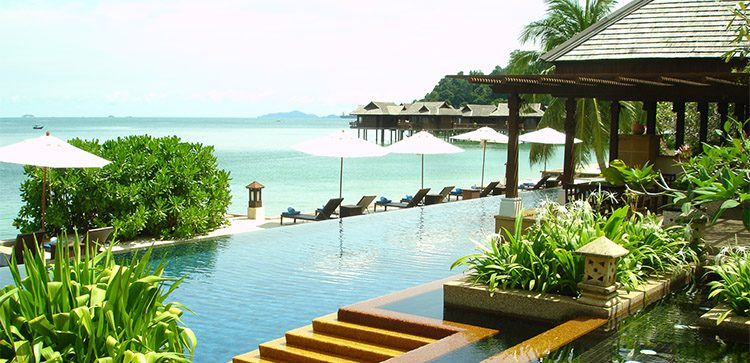 luxury resort with pool, lounge chairs and wooden pointed roofed terraces by the beach