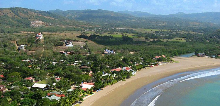 homes along the beach with lots of vegetation in nicaragua