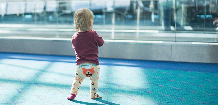 a toddler wearing bear pants at an airport