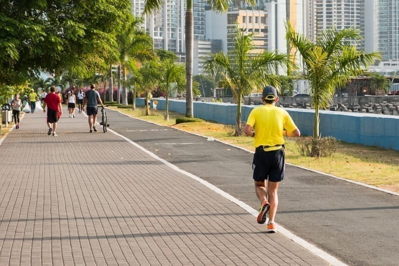 People running in public park with city skyline in background, Panama City, Panama