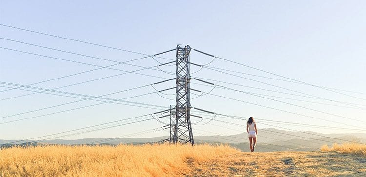 woman walking in a field with power lines