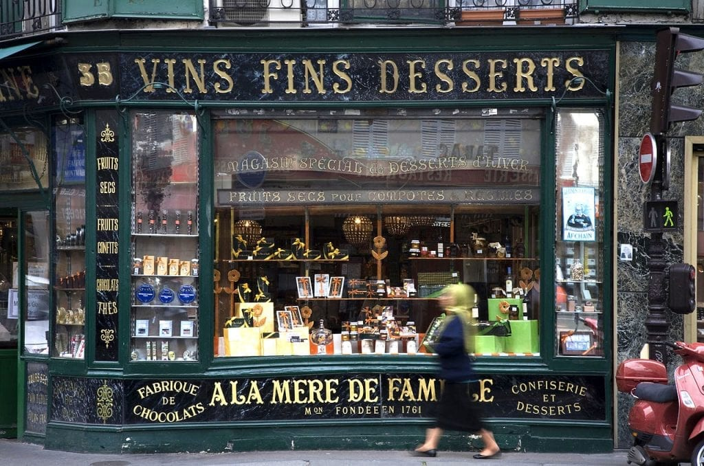 Woman walking past a wine and desserts shop