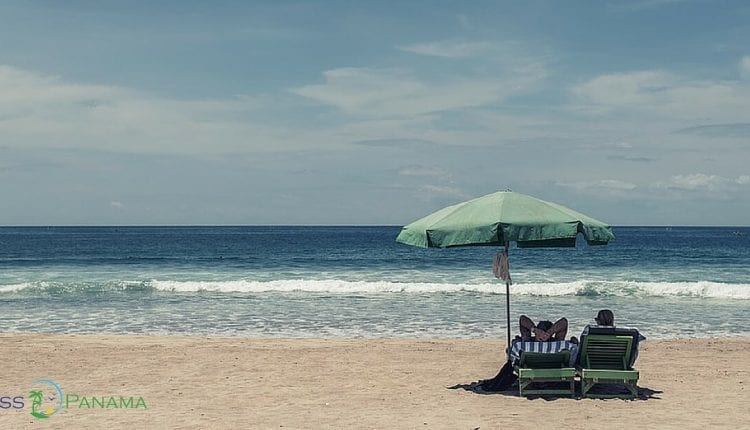 A Couple At The Beach Enjoying The Perks Of The Pensionado Discounts In Panama.