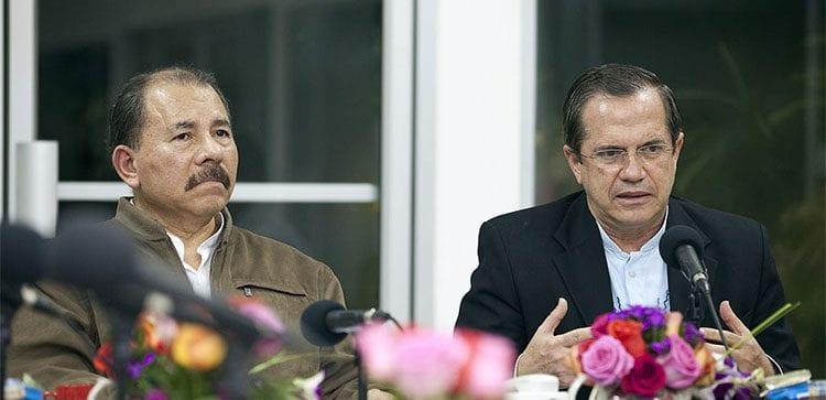 Nicaraguan President Daniel Ortega sitting at a table addressing the microphone