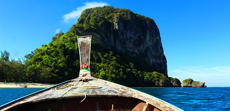 Longtail boat floating on the blue water of Thailand near the rocky cliffs.