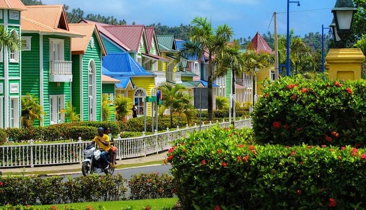 Man riding motorbike past Very colorful two story houses in Dominican Republic