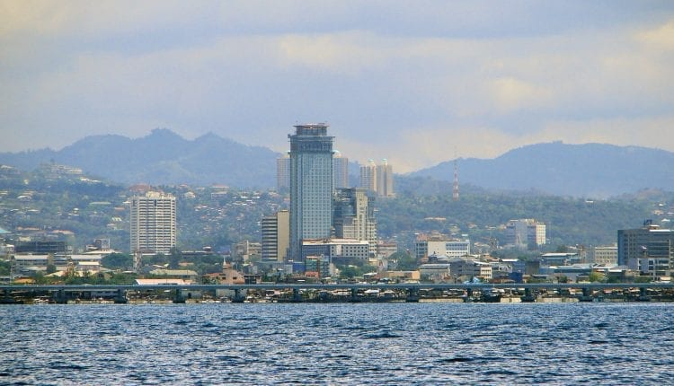 buildings and mountains as seen from the ocean in Cebu City
