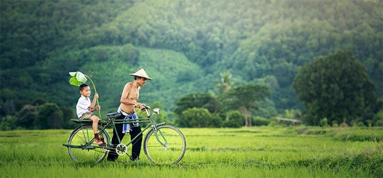 Father and son ride a bicycle with mountains in the background
