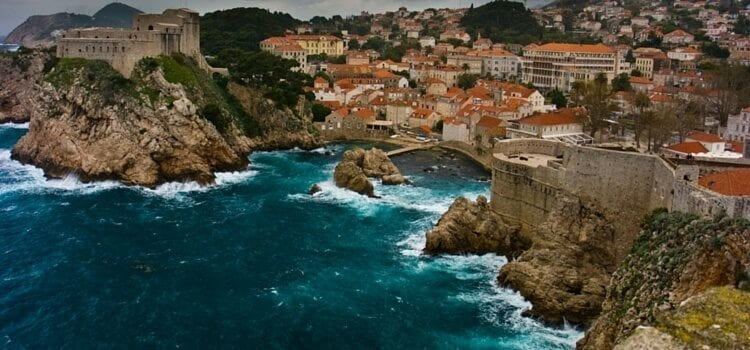 A view of the coast of Croatia with the orange roofed homes and blue ocean crashing against the rocky shores