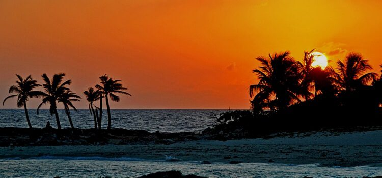 An ocean view of Mexico with the sun in the background.