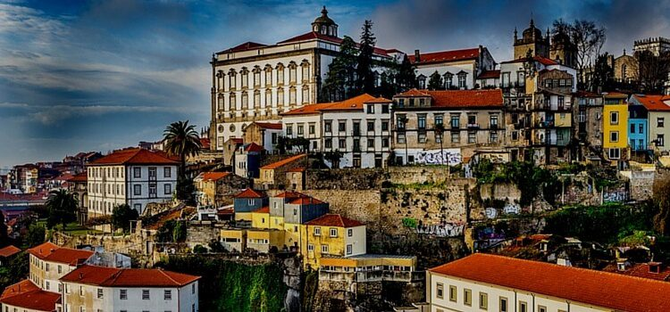 A hillside in Portugal with brightly colored buildings and a calm blue sky in the background
