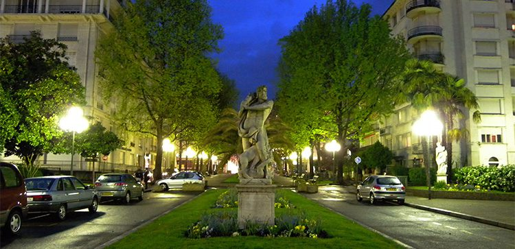 a night view of a statue in the median of Boulevard d'Aragon in Paris