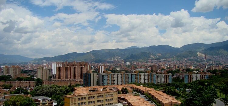A view of big, white clouds and the brick covered buildings of Medellin, Colombia