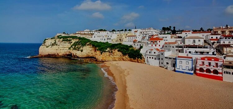 The Algarve Coast of Portugal complete with white houses that are trimmed with bright blues and reds