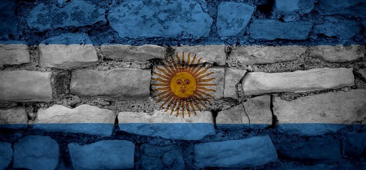 A brick wall with the Argentina flag painted over it.