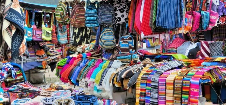 Market in Ecuador selling brightly colored fabrics, clothing, and other goods.