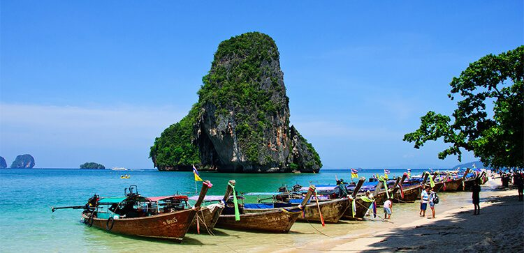 wooden long boats docked on a beach in thailand