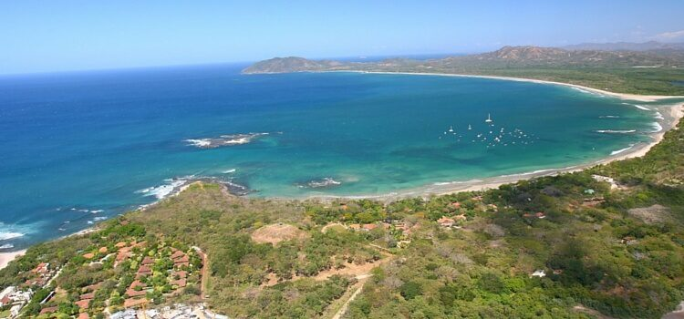 The coastline of Costa Rica with a bright blue ocean and the green land wrapping around