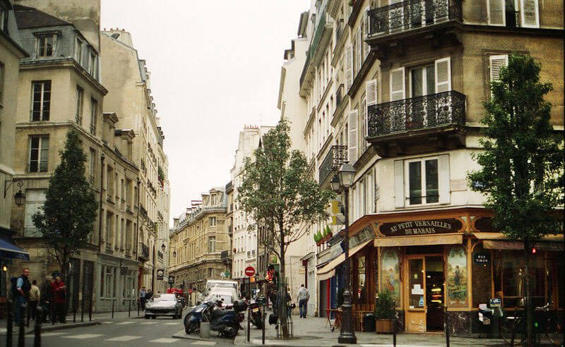a street corner in Paris with pedestrians, cards, and bikes