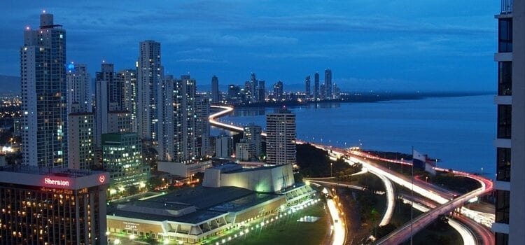 Panama City at dusk, with busy streets, buildings with a few lights on, and a city fast on the move.