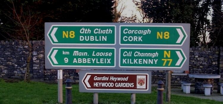 Road sign in Ireland with directional arrows pointing toward Dublin, Cork, Abbeyleix, and Kilkenny.