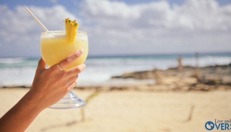 Relaxing In The Dominican Republic with a yellow drink in hand at the beach