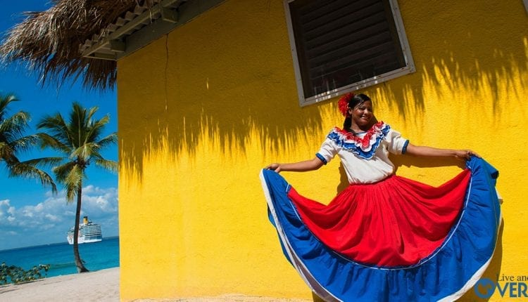 Catalina Island, Dominican Republic. A woman in traditional outfit in front of a bungalow on a seashore.