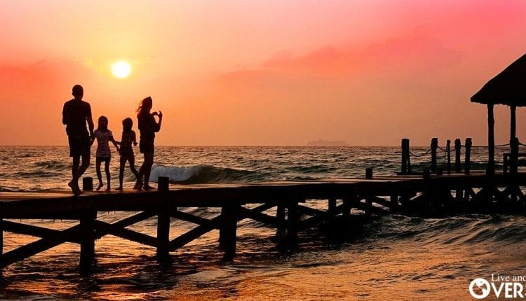 An entrepreneur and his family walking along a pier as the sun goes down in the Dominican Republic