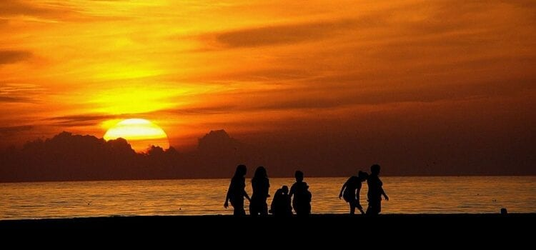 A family living in Mexico enjoying a day at the beach with a bright orange sun going down in the distance.
