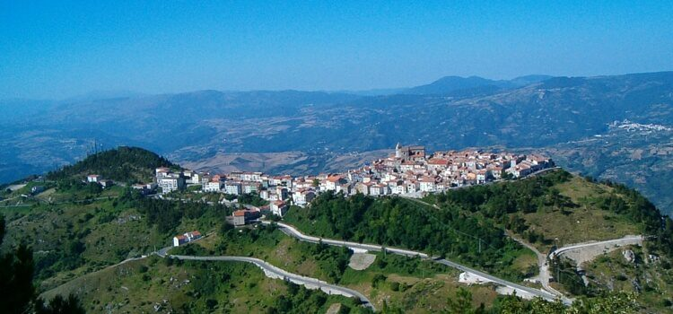 An aerial view of Abruzzo, Italy with a town on a hilltop and mountains in the distance