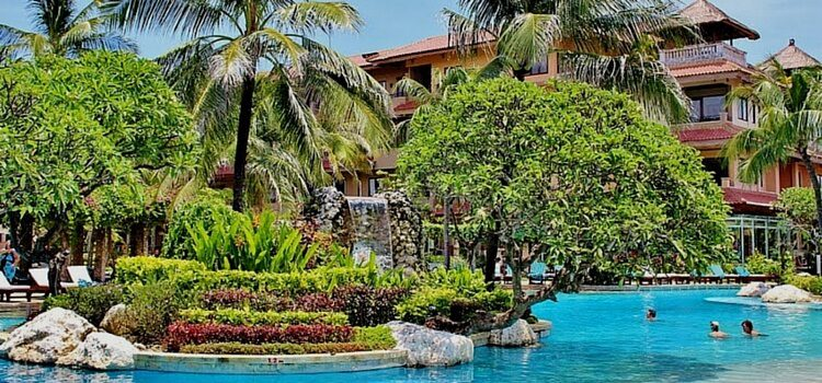 View of Bali, Indonesia with bright blue water and lush green trees.