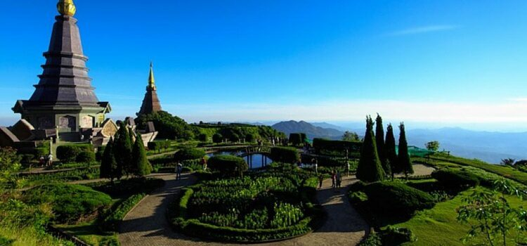 A mountain top view over Chiang Mai, Thailand with beautiful green gardens and a golden-topped temple