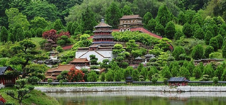 A hillside with a temple in China with water in front and
