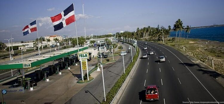 The economy of the Dominican Republic is fast moving with a multiple lane highway and full service gas station in view, as well as the Dominican Republic flag flying high
