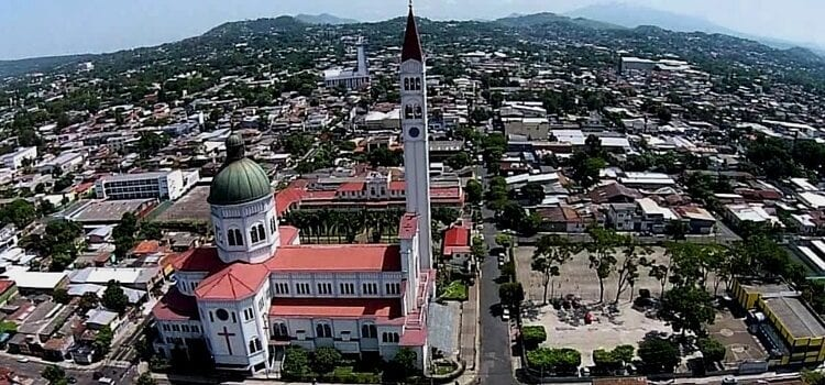 An aerial view of El Salvador showing off the beautiful cityscape and mountains in the background