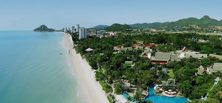 Hua Hin, Thailand from the sky, with is soft blue waters, white sand beaches, and lush green trees popping up in between the buildings