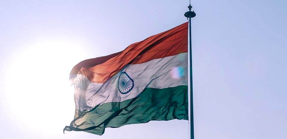 the india flag flapping in the wind against a sunny sky
