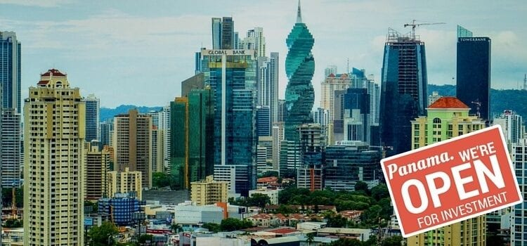 "A skyline view of Panama City with a red sign saying, ""Panama. We're Open For Investment."""