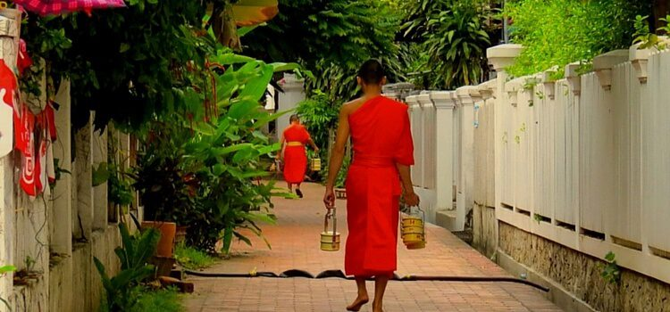 A monk from Laos wearing an orange robe and walking with two buckets in his hands