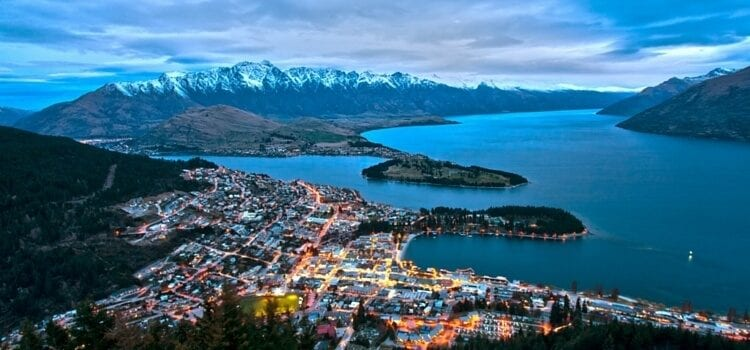 A view over a city in New Zealand at dusk with mountains and water in the background