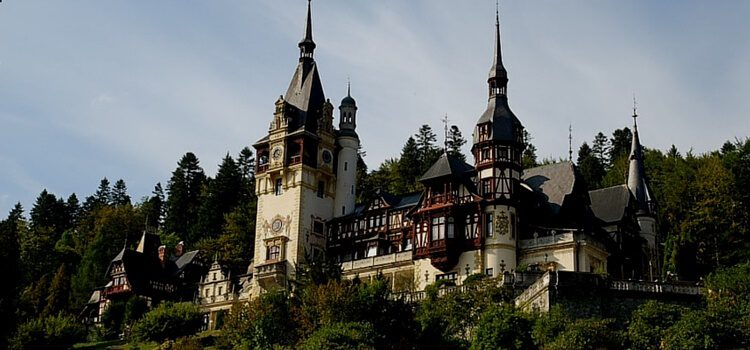 A castle nestled in the hills and green foliage of Romania
