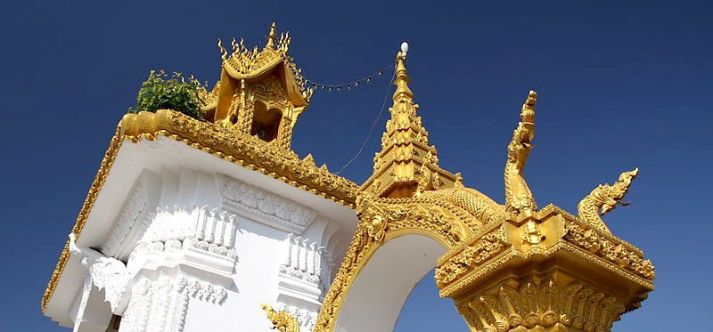 a gold roofed buddhist temply against a blue sky