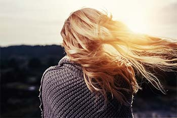 the back view of a blond woman's hair is flapping in the wind