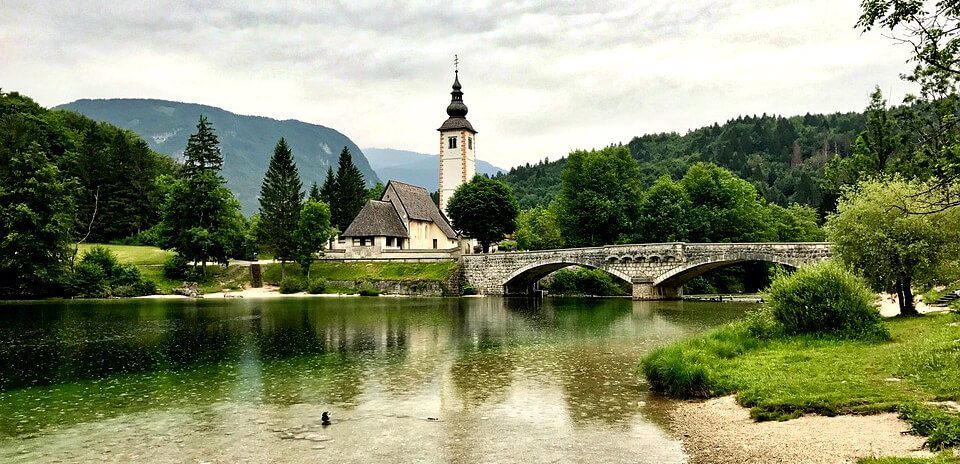 A church with a tall steeple next to a stone bridge and lake surrounded by lush green hills