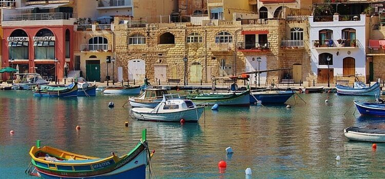 Traveling in Malta by colorful boats that reflect off the calm blue waters.